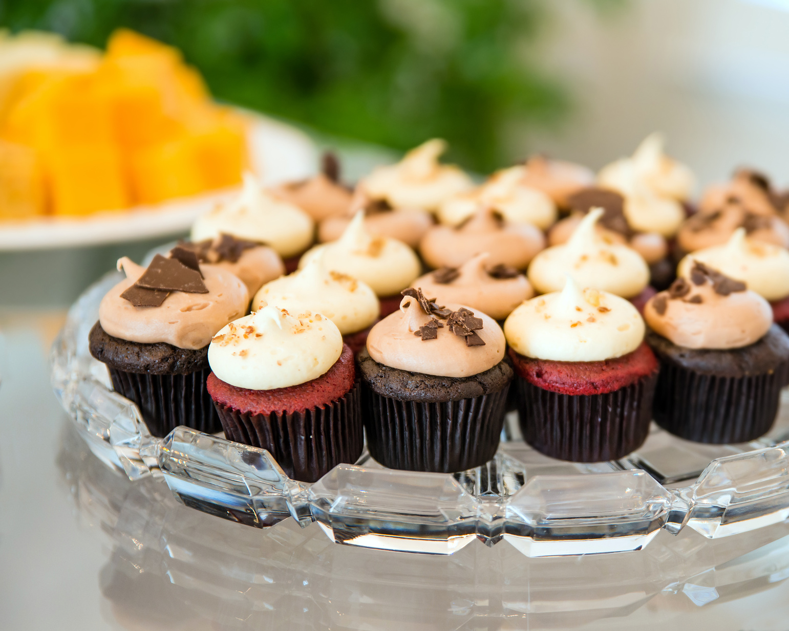 Mini cupcakes in glass tray on buffet