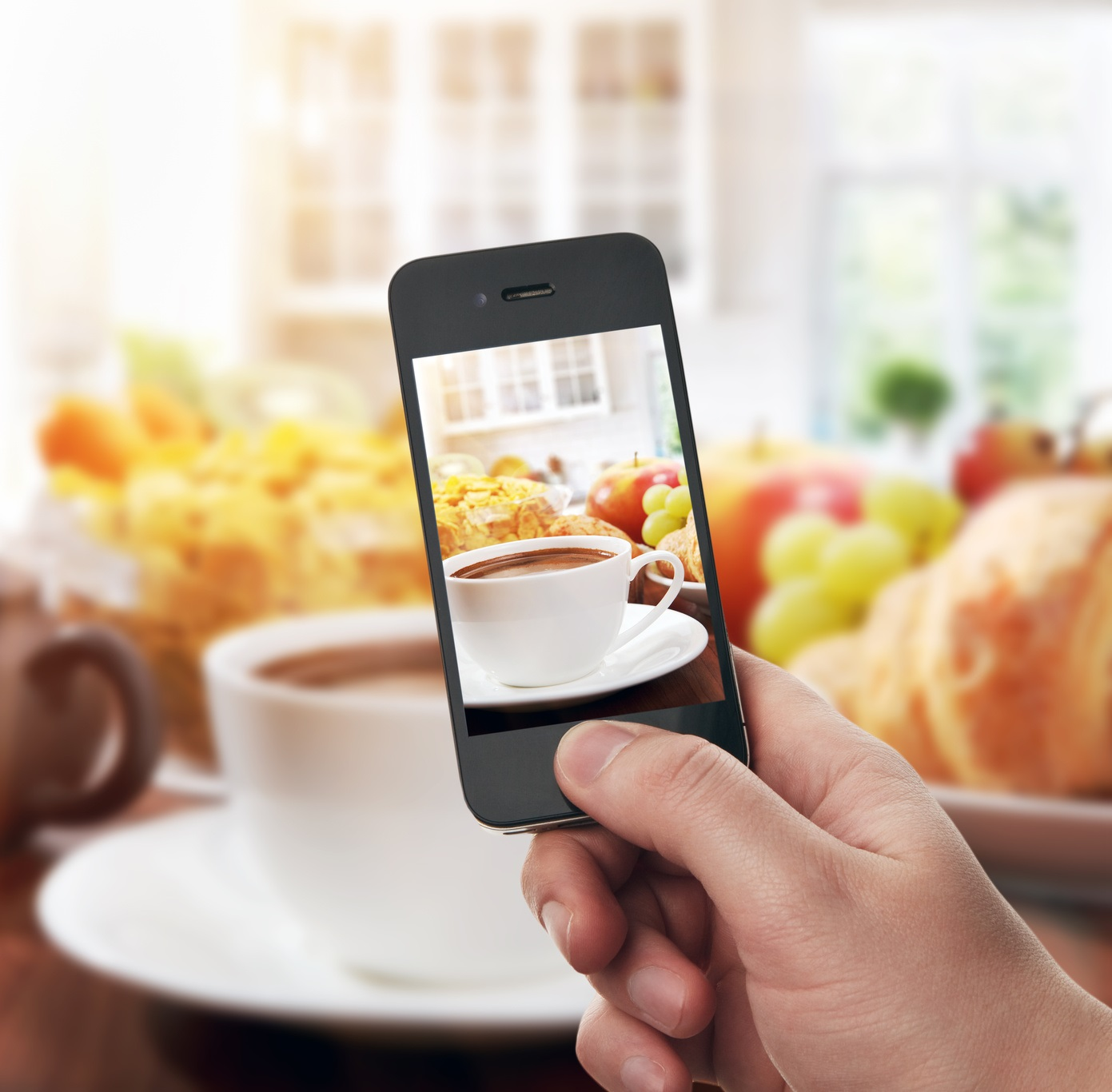 Hand with smartphone taking food photo of fresh healthy breakfast with cup of coffee