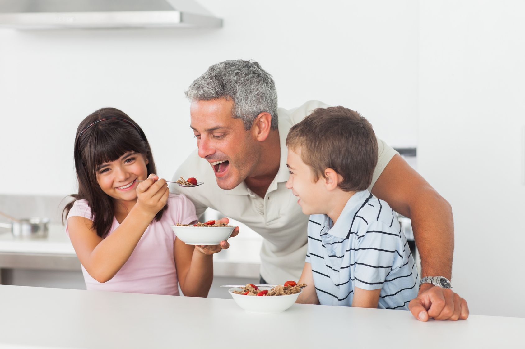 Little girl giving cereal to her father with brother smiling in kitchen