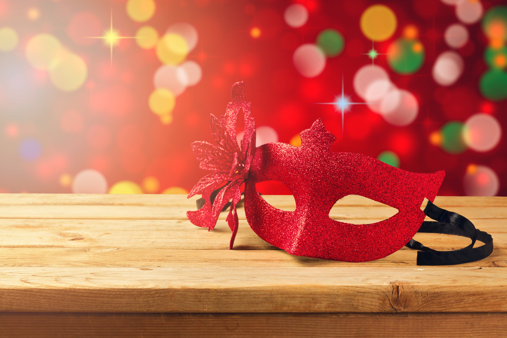 Carnival mask on wooden table over bokeh background