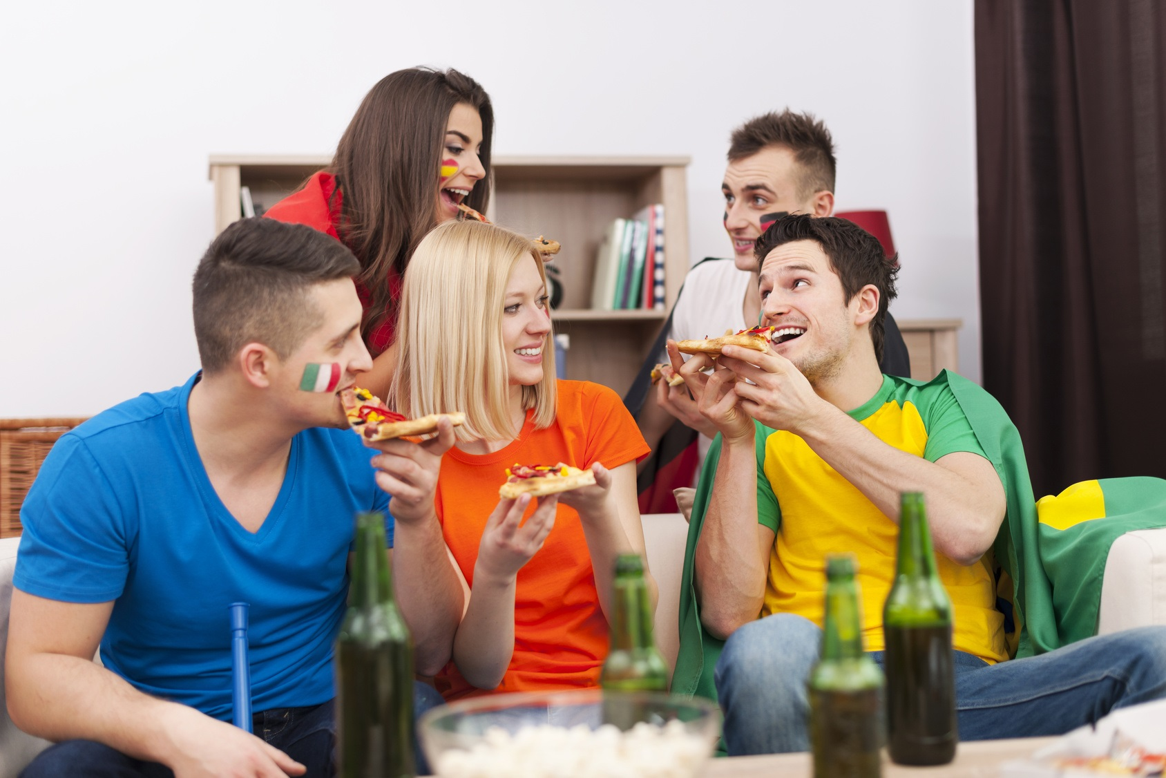 Group of multinational people eating pizza during the break in football match